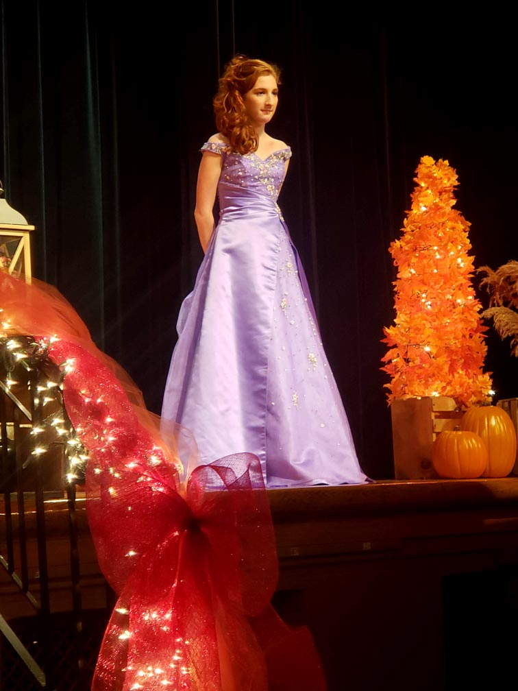 student posing for fashion show in purple dress